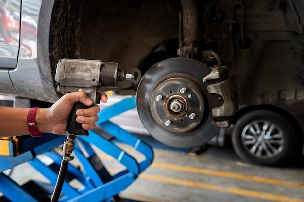 Homem mecânico de automóveis com chave de fenda elétrica, trocando o pneu na oficina mecânica.