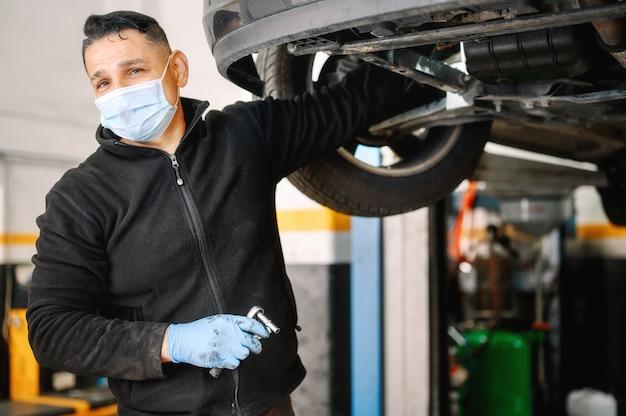 Homem mecânico de automóveis com máscara facial, trabalhando na oficina mecânica.