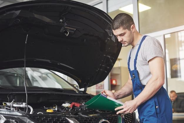 Homem mecânico de automóveis ou ferreiro com prancheta na oficina.