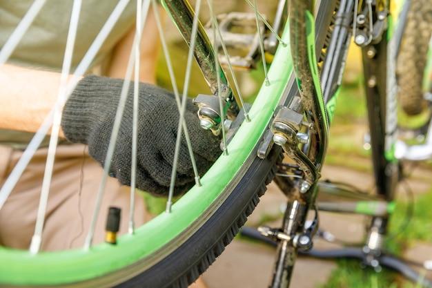 Homem mecânico de bicicleta conserta bicicleta em oficina de bicicletas, mão ao ar livre de ciclista ciclista examina ...