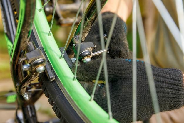 Homem mecânico de bicicleta conserta bicicleta na oficina de bicicletas, ao ar livre. mão do ciclista, o ciclista examina, corrige o sistema de transmissão do ciclo moderno. manutenção de bicicletas, conceito de loja de esporte.