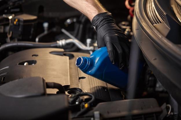 Homem mecânico de luvas derramando óleo no motor do carro