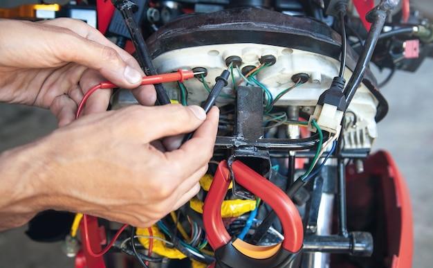 Homem mecânico fiação da motocicleta de cabos elétricos.