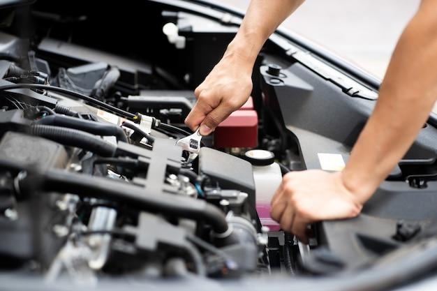 Homem mecânico trabalhando e reparando o motor do carro no centro de serviço do carro.