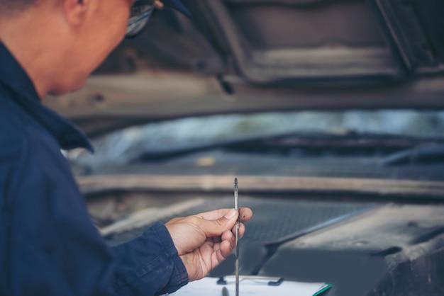Homem mecânico verifica os pneus do carro ao ar livre no local de serviço na garagem de automóveis para centro automotivo