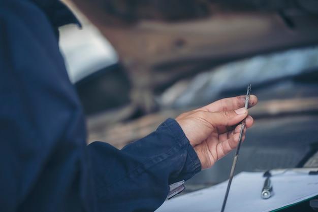 Homem mecânico verifica os pneus do carro ao ar livre no local de serviço na garagem de automóveis para centro automotivo Foto Premium