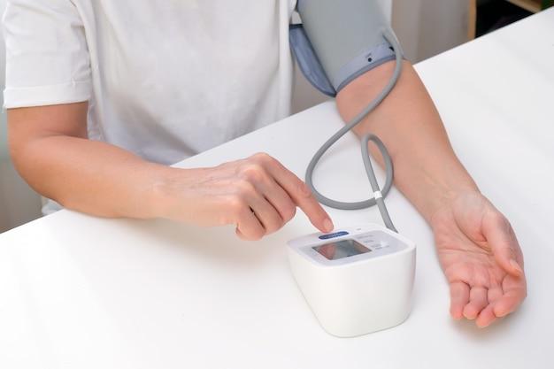 Homem mede a pressão arterial, fundo branco. hipotensão arterial. mão e tonômetro fecham.