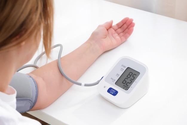 Homem mede a pressão arterial, fundo branco. hipotensão arterial