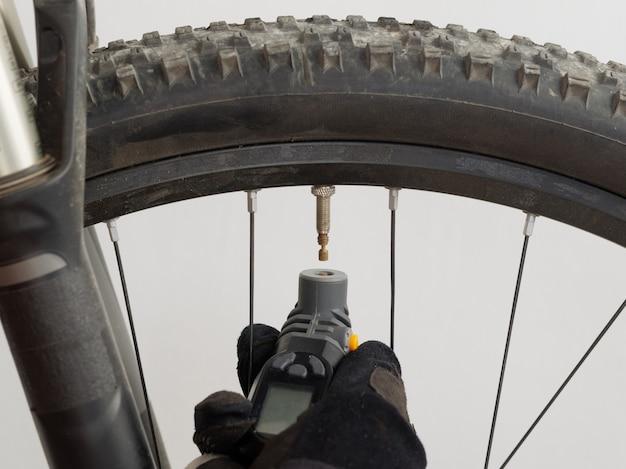 Homem mede a pressão dos pneus no mountain bike manômetro eletrônico.