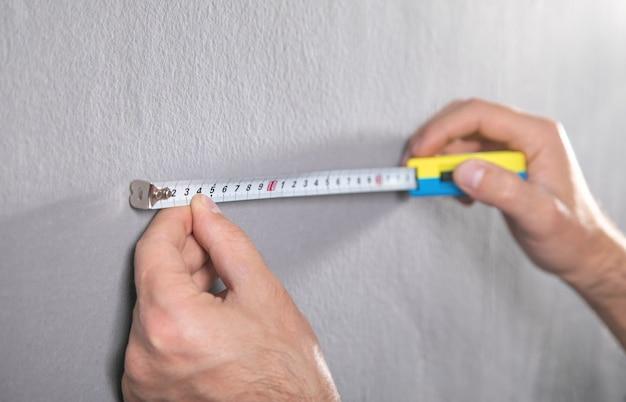Homem mede uma parede cinza com fita métrica.