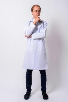 Homem médico com cabelo loiro e óculos contra uma parede branca