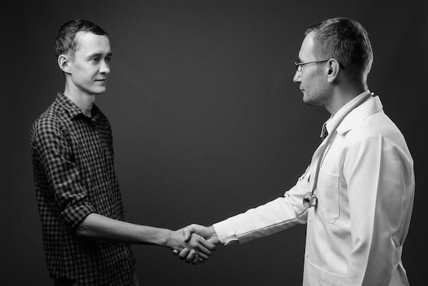 Homem médico e jovem paciente contra uma parede cinza em preto e branco
