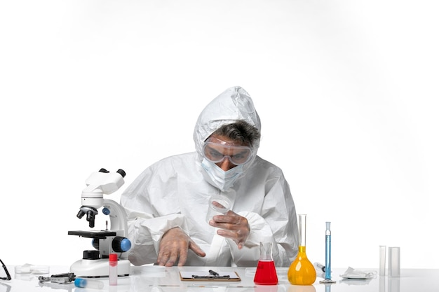 Homem médico em traje de proteção com máscara estéril segurando frasco em branco claro