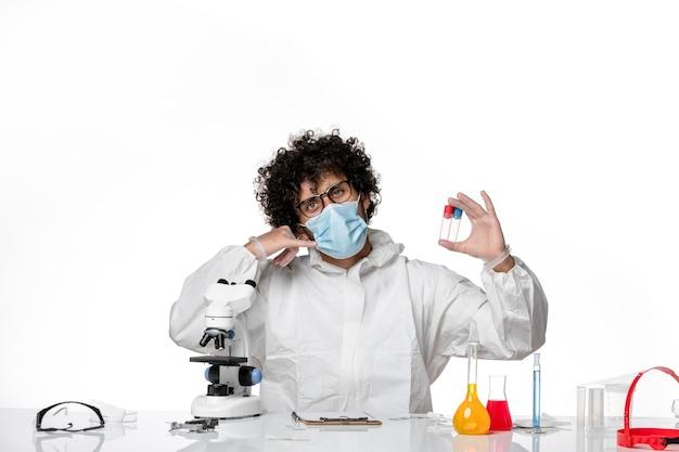 Homem médico em traje de proteção e máscara segurando frascos em branco