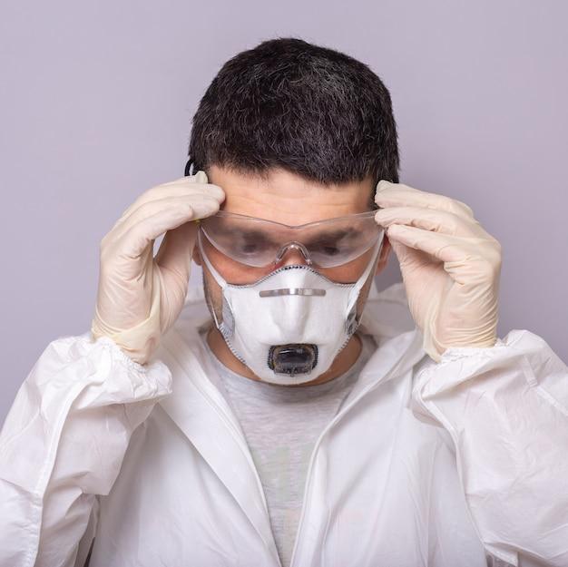 Homem, médico remove óculos, traje de proteção contra infecções bacterianas e virais, covid 19, durante a pandemia, máscara para proteção, luvas de borracha param, ficam em casa close-up