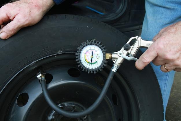 Homem, medindo a pressão dos pneus