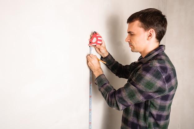 Homem medindo e marcando a distância na parede branca com fita métrica e lápis