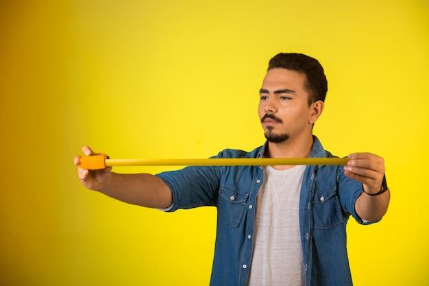 Homem medindo o comprimento pela régua e olhando atento.