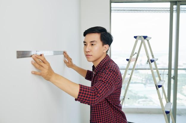 Homem medindo paredes