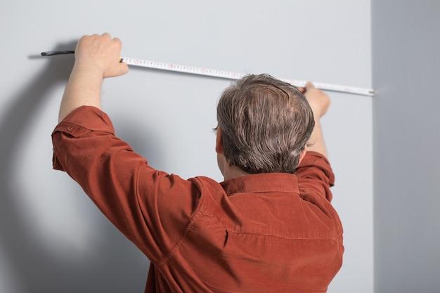 Homem medindo uma parede cinza com fita isolante