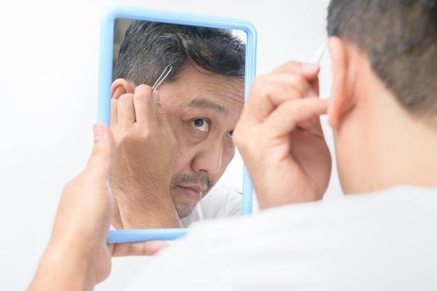 Homem médio asiático se olha no espelho e usa uma pinça para arrancar seus cabelos grisalhos, isolados no fundo branco. conceito de saúde