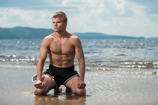 Homem medita na praia depois de um treino