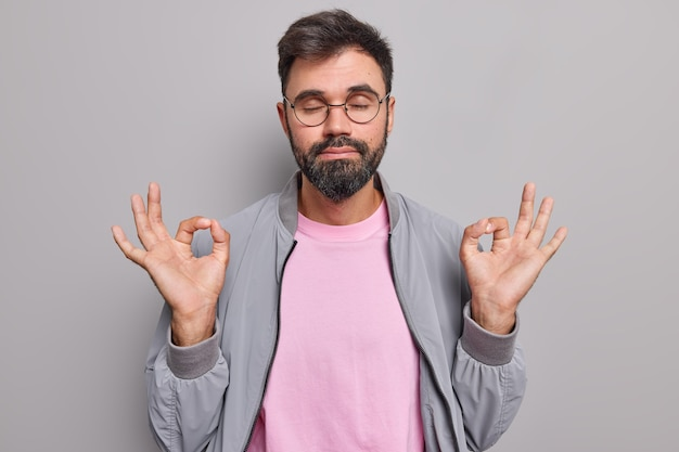 Homem medita sozinho faz gesto certo com ambas as mãos respira profundamente mantém os olhos fechados pratica ioga usa óculos redondos jaqueta cinza camiseta rosa