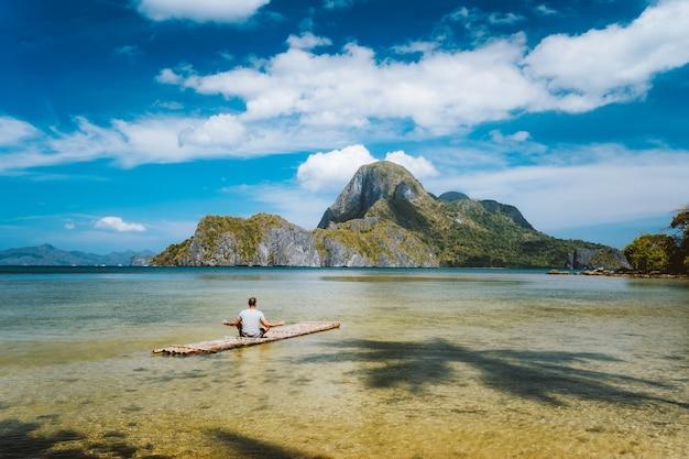 Homem meditando em um flutuador de bambu cercado por águas rasas da lagoa e a baía das ilhas de cadlao em um