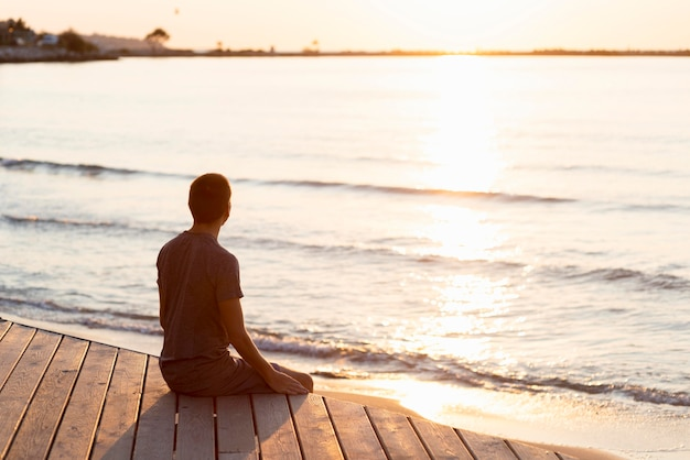 Homem meditando na praia