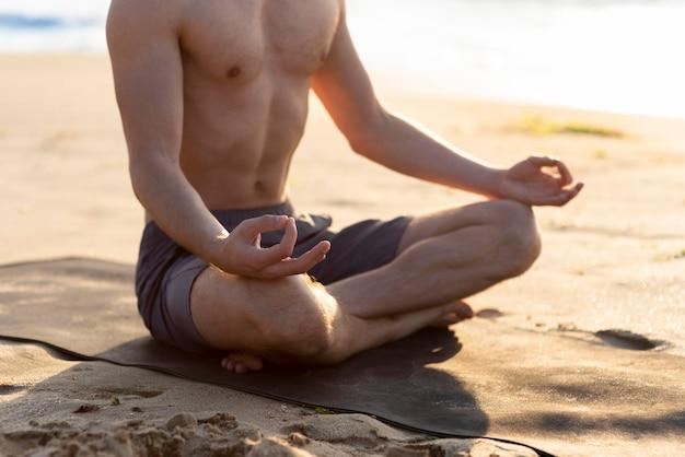 Homem meditando sem camisa na praia