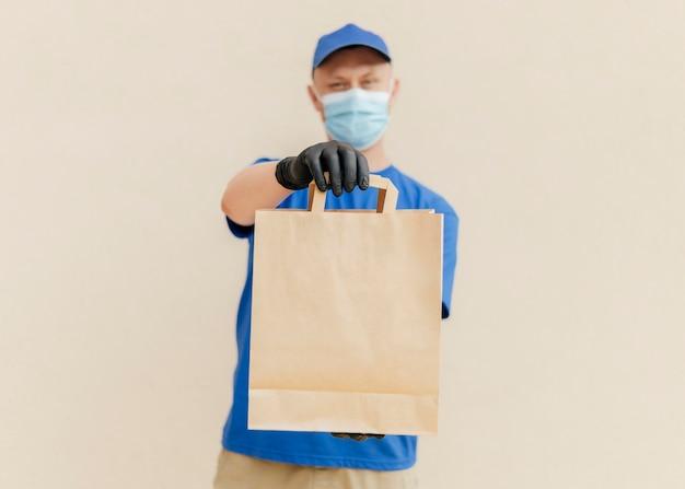Homem meio embaçado segurando um saco de papel