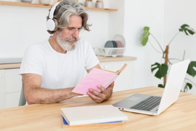 Homem meio tiro, escrivaninha, olhando livro