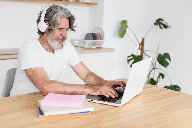 Homem meio tiro, escrivaninha, usando computador portátil