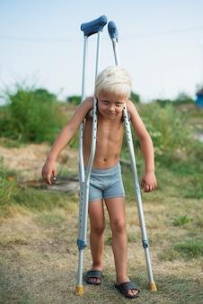 Homem menino, sem, um, camisa, ficar, ligado, muletas, ao ar livre