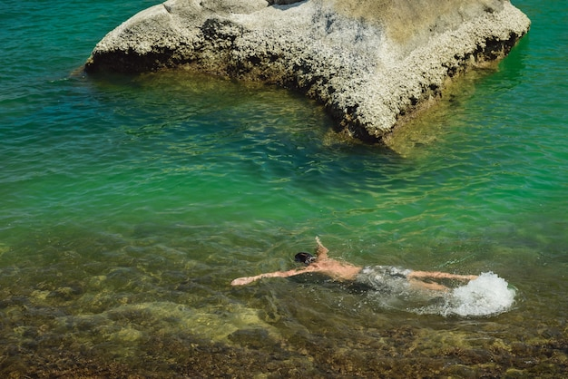 Homem, mergulho com snorkel nas águas claras do mar na tailândia, na ilha de phangan. as pessoas vivem uma vida saudável e descansam em condados tropicais. rapaz deitado nas ondas a observar peixes