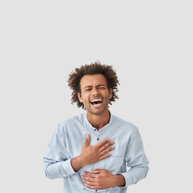 Homem mestiço, amigável e brincalhão, aperta os olhos e ri alto, mantém as mãos na barriga, não para de rir enquanto ouve algo engraçado, posa contra uma parede branca, tem cabelo afro encaracolado