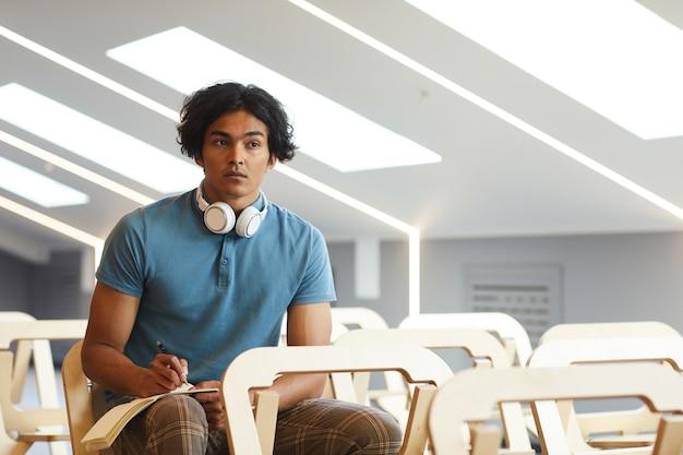Homem mestiço concentrado com fones de ouvido ao redor do pescoço, sentado em um auditório vazio e fazendo anotações na apostila