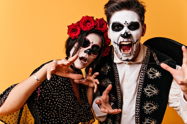 Homem mexicano gritando e sua namorada com maquiagem de halloween assustadoramente posando para o retrato.
