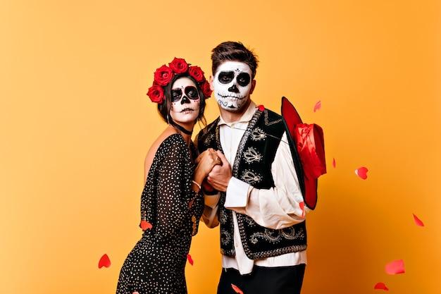Homem mexicano morto com sombrero de mãos dadas com a namorada. casal de zumbis isolados na parede amarela.