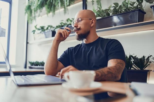 Homem milenar caucasiano trabalhando no computador em casa segurando uma caneta em seu trabalho à distância