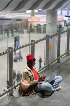 Homem milenar elegante viajante afro-americano, descansando e sentado no chão no aeroporto, usando o celular.