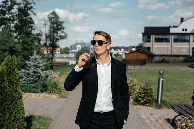 Homem milionário em um terno caro sob medida, sentado ao ar livre com óculos e segurando uma taça de vinho tinto,