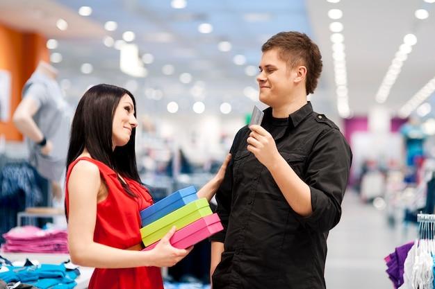 Homem mimando a namorada comprando roupas novas para ela