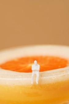 Homem minúsculo sentado à beira de um coquetel de margarita de laranja