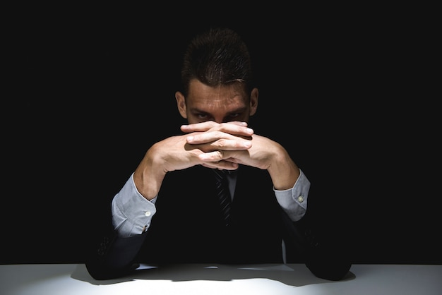 Homem misterioso com as mãos entrelaçadas, olhando da sombra escura