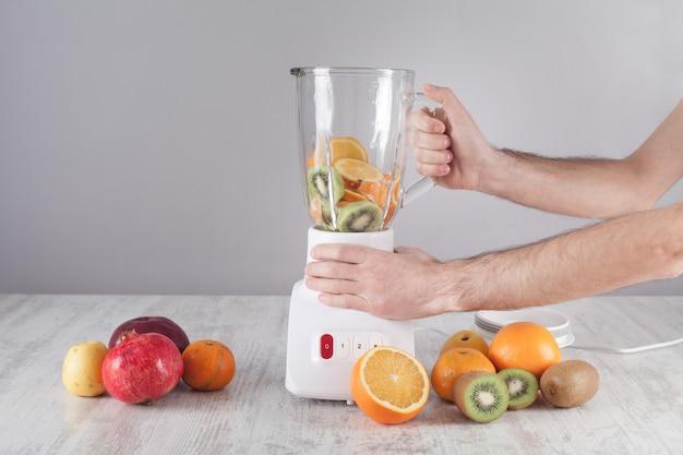 Homem misturando frutas com o liquidificador.