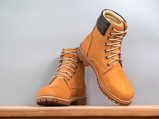 Homem moda amarelo botas couro isolado em madeira na cinza