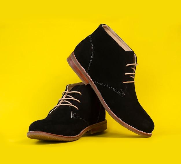 Homem moda preto tornozelo botas couro isolado em amarelo