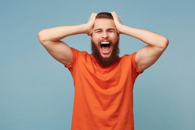 Homem modelo segurando sua cabeça com as mãos grita alto, expressão facial de raiva, isolada no azul.