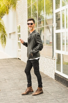 Homem moderno, com, mãos, em, seu, bolso, segurando, esperto, posição telefone, frente, porta
